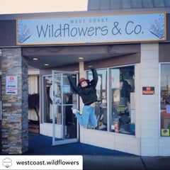 Alissa jumping in excitement in front of the Wildflowers & Co. shop