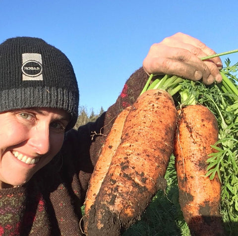 Emily smiling and holding up freshly dug up carrots.