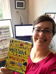 Smiling Keeley holding up a copy of the book The Vegetable Museum