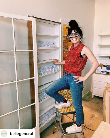 Shop owner Katie on a ladder in front of the seed display wall at the shop.