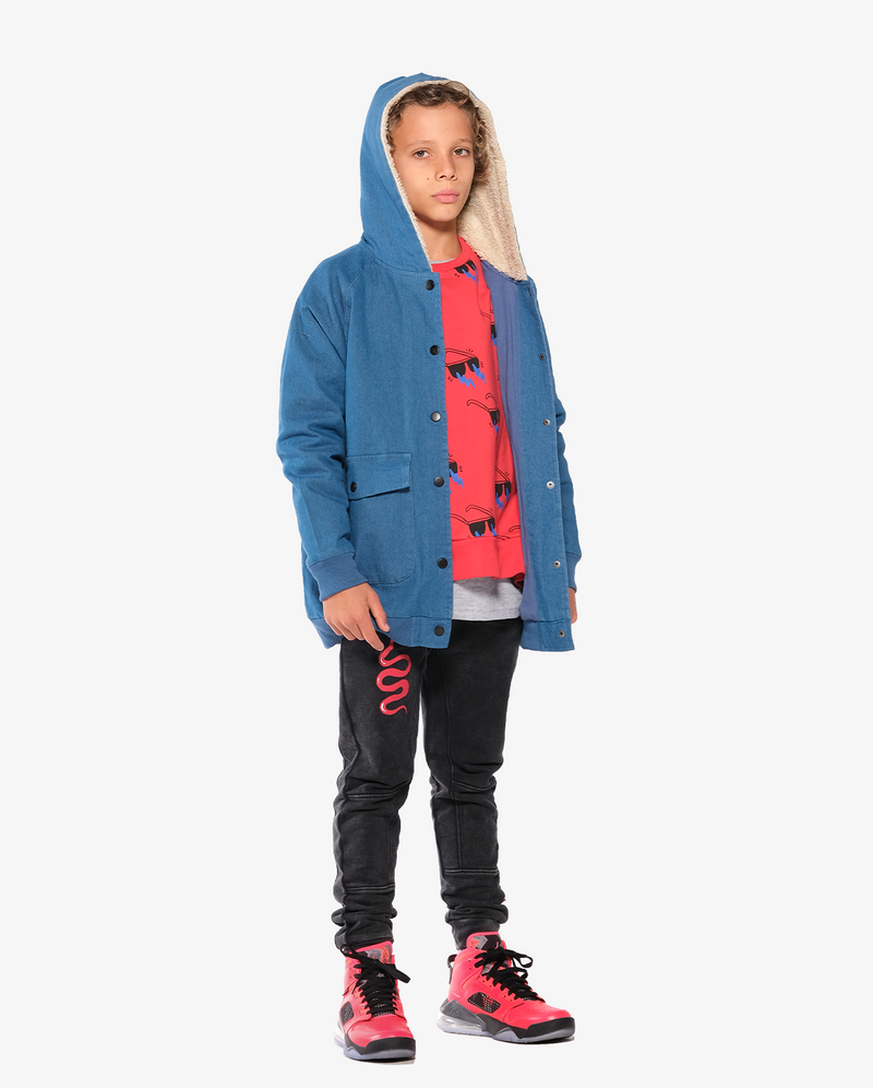 Bandits by Band of boys Lightning Tiger Bomber Jacket with faux fur lined hood on model with hood on. Model also wears lightning sunnies crew tee and Red viper trackies - side view.