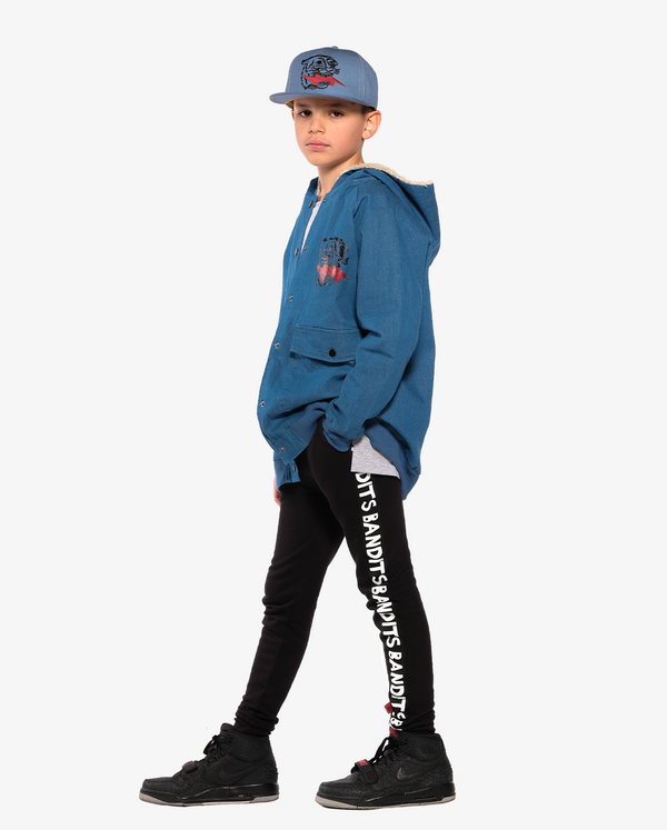 Bandits by Band of Boys Tape Skinny Trackies on model - side on. Model also wears Lightning Tiger Cap and lightning tiger Bomber Jacket
