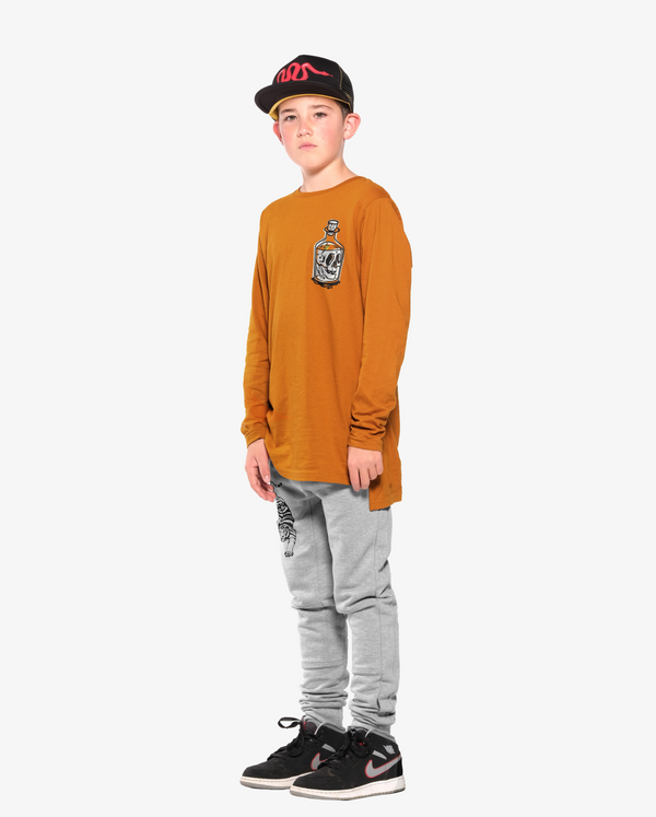 Bandits by Band of Boys Ochre Long Sleeve Step Hem on model. Model also wears Black Trucker cap with red viper along with Grey Crouching Tiger Panel Trackies.