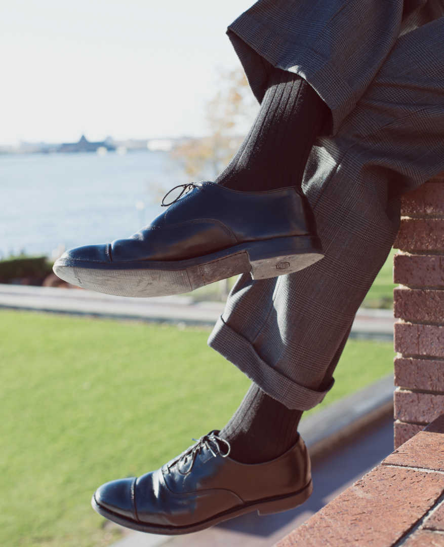 black merino wool over the calf dress socks paired with charcoal grey trousers and black dress shoes