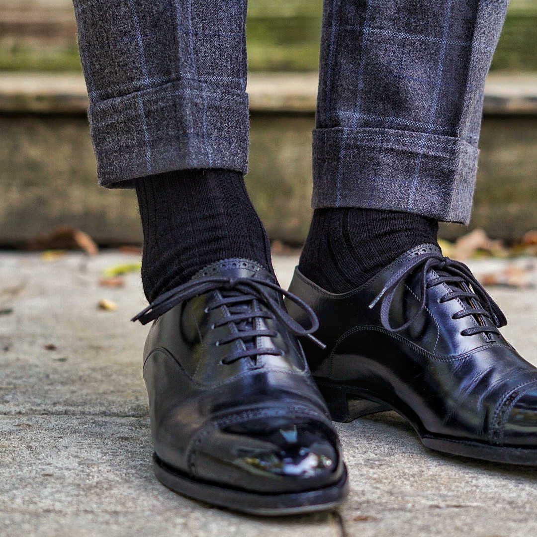 man standing wear black merino wool dress socks and black mirror-shined dress shoes with charcoal grey windowpane trousers