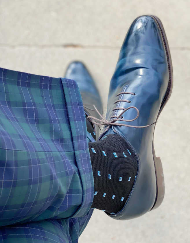 man wearing blue plaid dress pants crossing his legs with bright blue dress shoes and black and blue merino wool dress socks