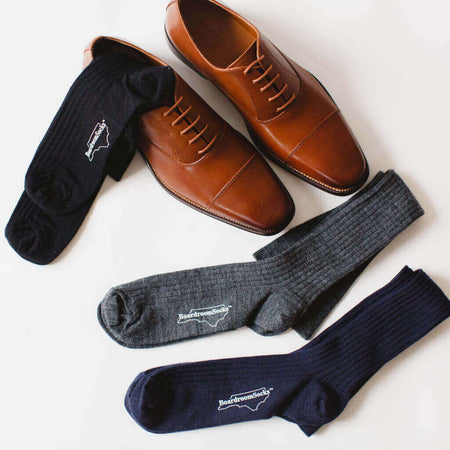 Three Pairs of Over the Calf Dress Socks Laying on a Pair of Brown Dress Shoes