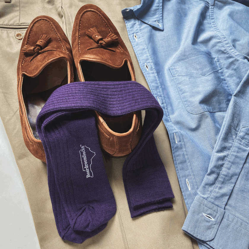 purple merino wool dress socks laying on brown suede tassel loafers with khaki pants and light blue oxford