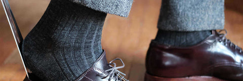 man wearing charcoal merino wool dress socks and putting on dress shoes with a shoe horn