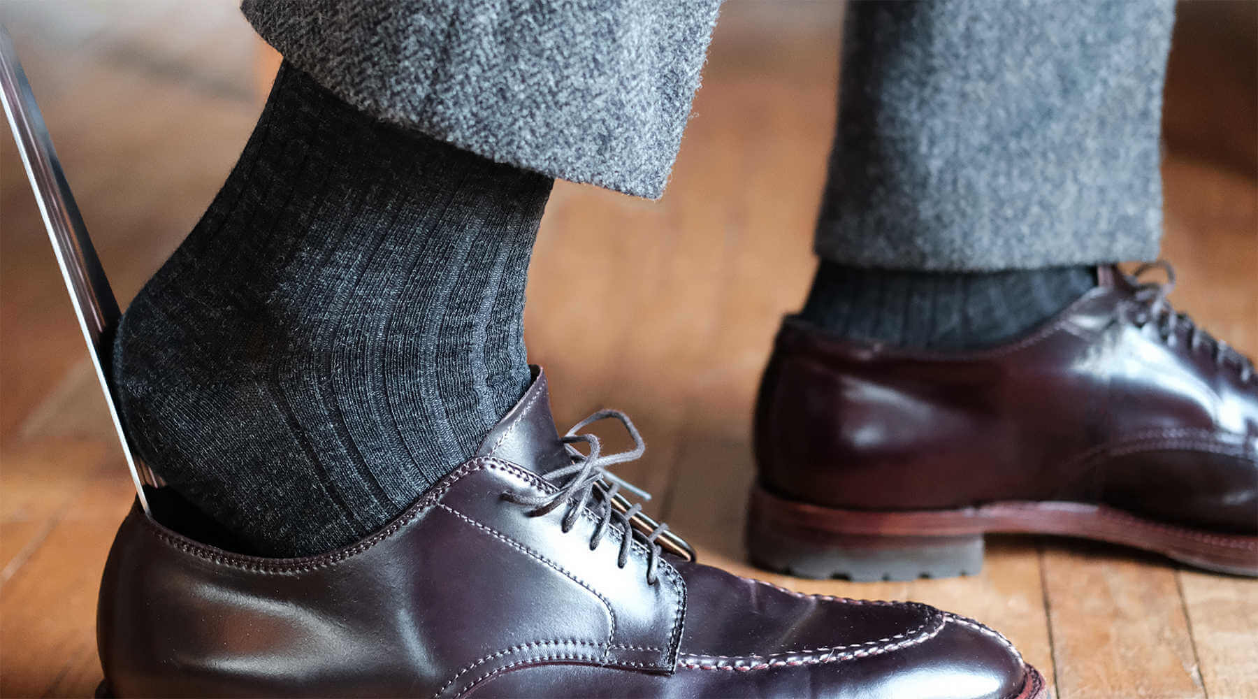 man wearing ribbed charcoal merino wool dress socks using shoe horn to put on alden dress shoes