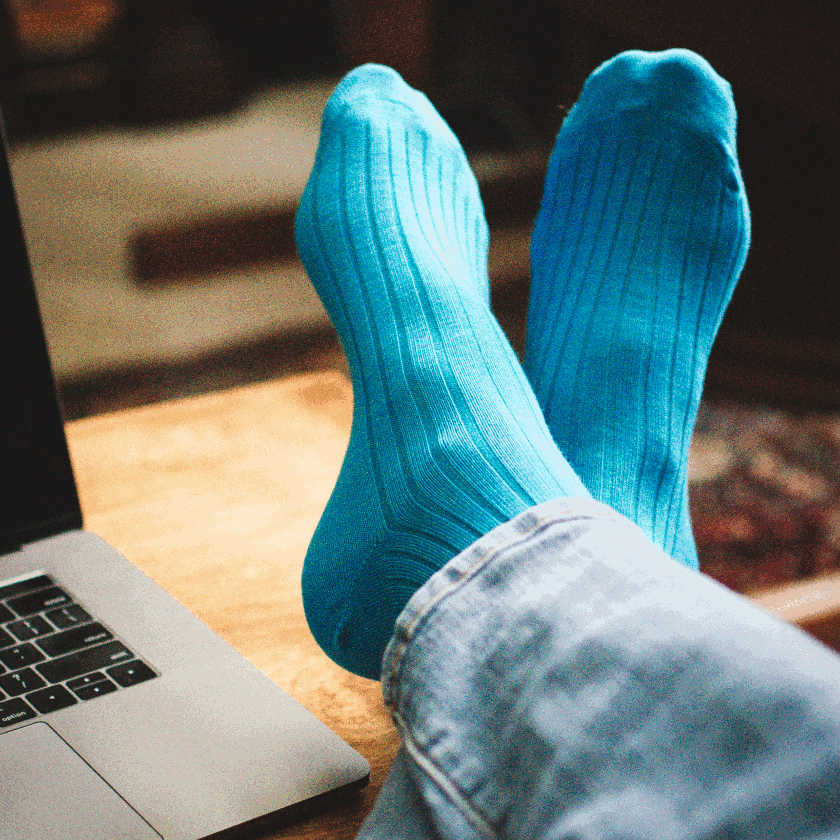 man crossing ankles with feet up on desk wearing bright teal dress socks