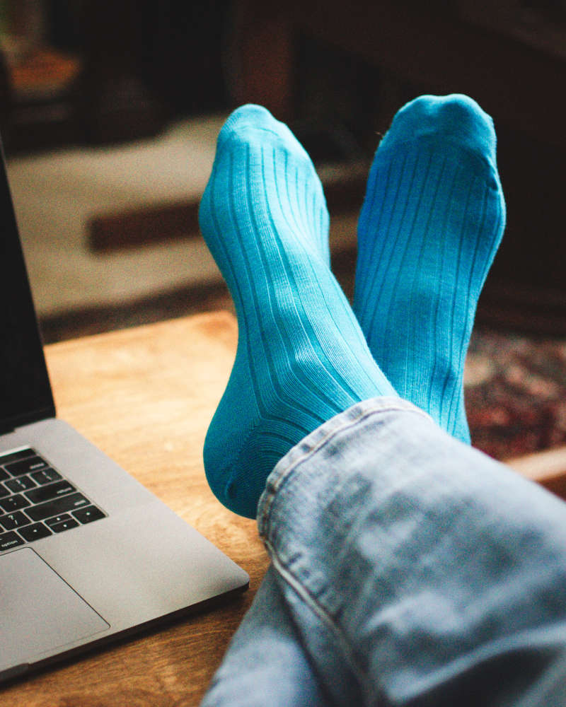 man wearing bright teal blue dress socks with feet crossed up on desk