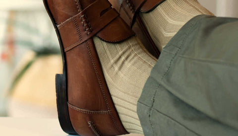 man crossing ankles while wearing khaki dress socks and brown loafers