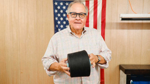 Mike holding a cone of charcoal wool in front of an American flag