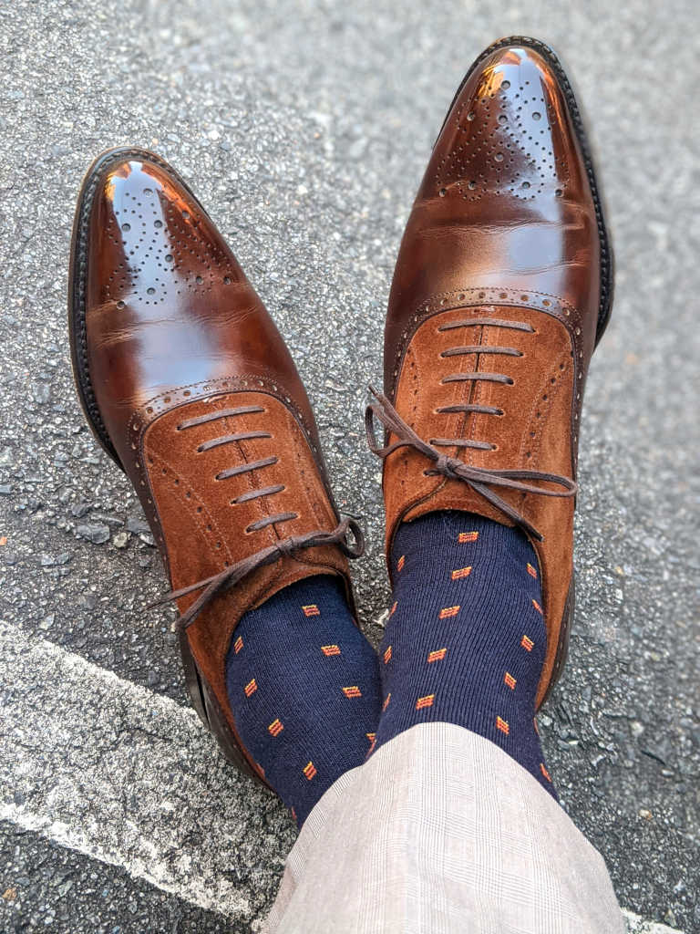 man wearing light tan dress pants crossing ankles while wearing navy blue wool dress socks accented with orange squares