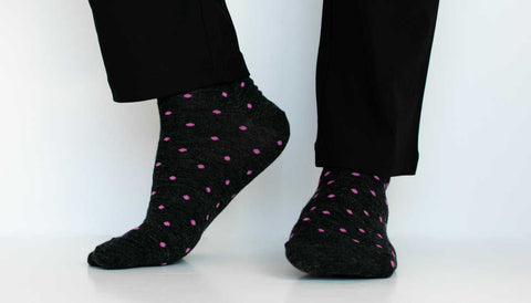 man wearing black trousers and charcoal grey dress socks accented with pink polka dots