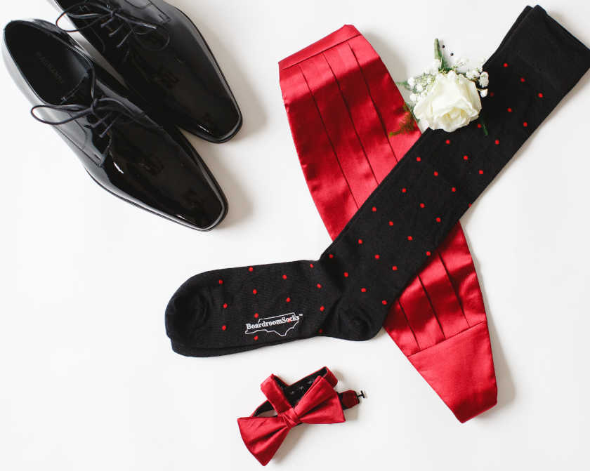 black over the calf dress socks with bright red polka dots paired with formal menswear
