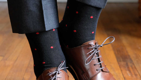 man wearing black dress socks with small red polka dots