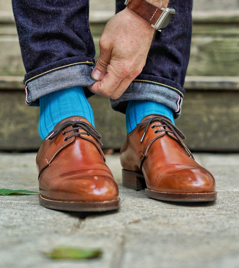 man wearing smartwatch adjusting cuff of jeans while wearing bright teal wool dress socks and light brown dress shoes