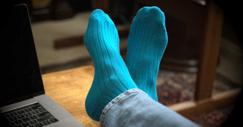man crossing his leg and putting feet up on desk while wearing teal dress socks