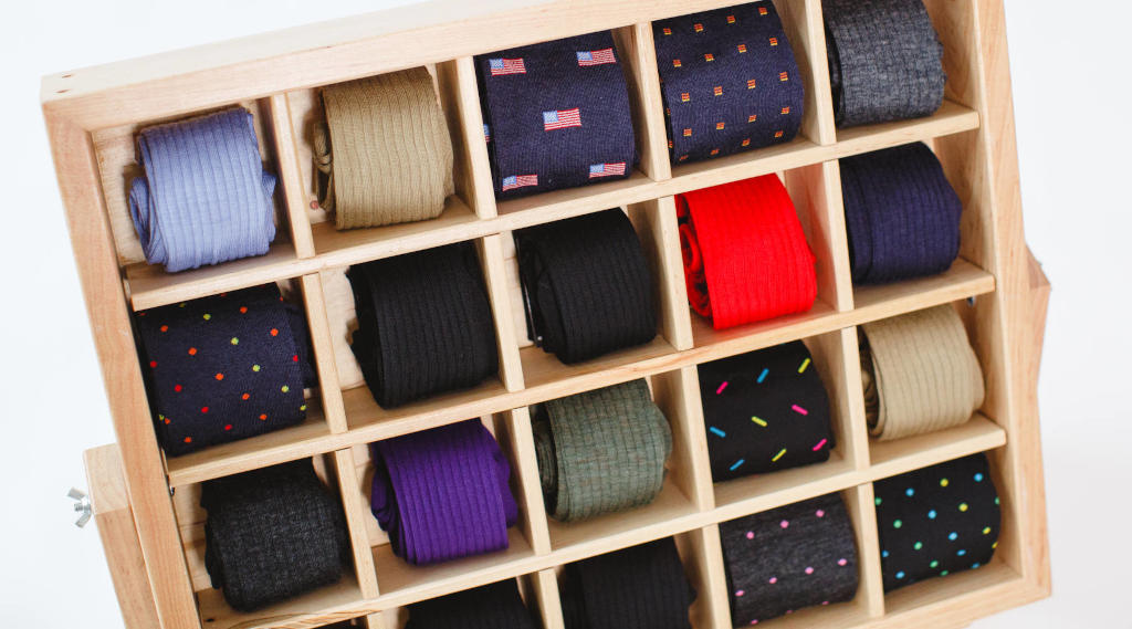 colorful dress socks for men rolled up and arranged in a wooden display