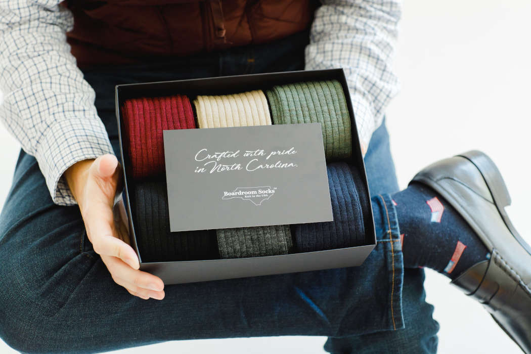 man holding gift box full of colorful merino wool dress socks
