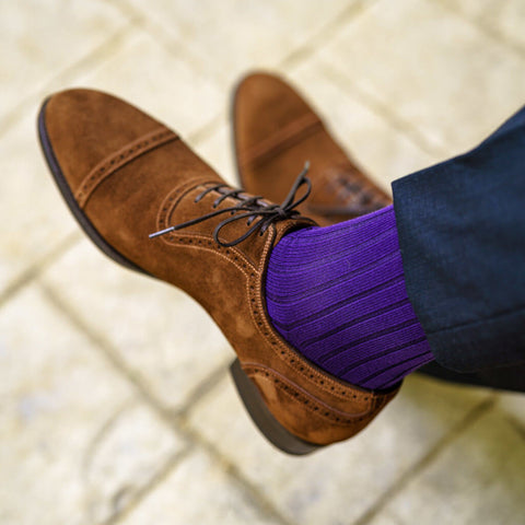 purple socks with navy blue dress pants and brown suede shoes
