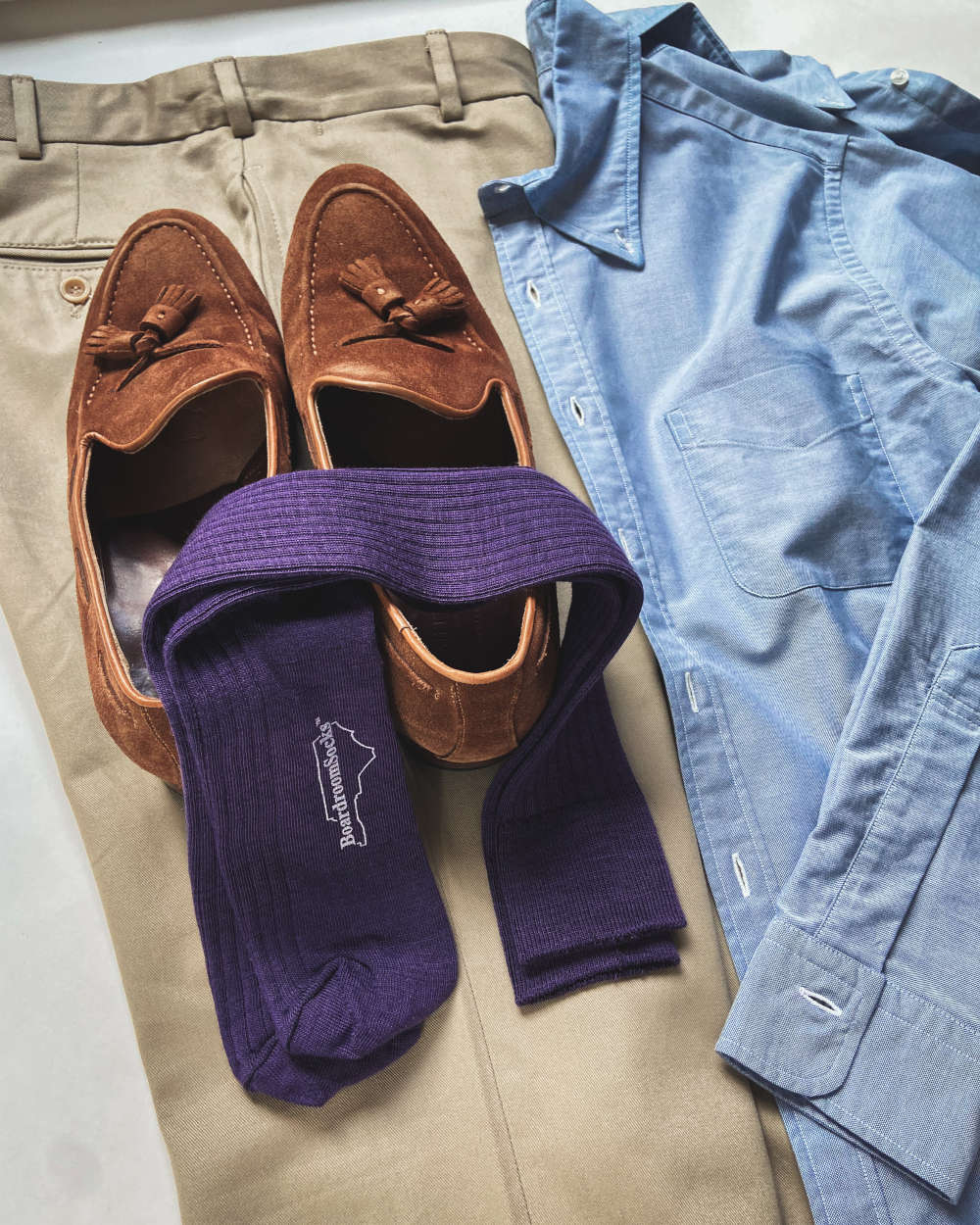 purple merino wool over the calf dress socks laying on a pair of brown suede loafers and khakis