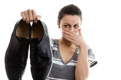 woman holding smelly black dress shoes