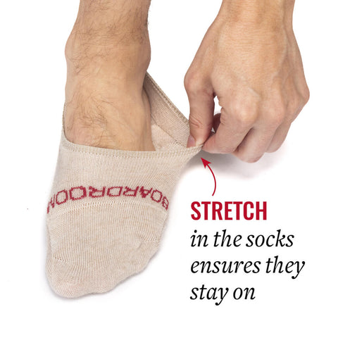 man pulling on stretchy no-show socks demonstrating that stay on