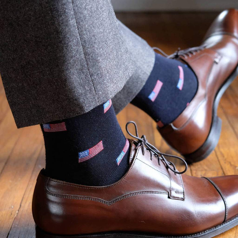 Man Wearing Grey Dress Pants and Dark Brown Dress Shoes with Navy Blue Dress Socks Accented with Small American Flags