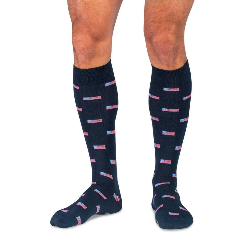 Model Wearing Navy Blue Over the Calf Dress Socks Decorated with Small American Flags
