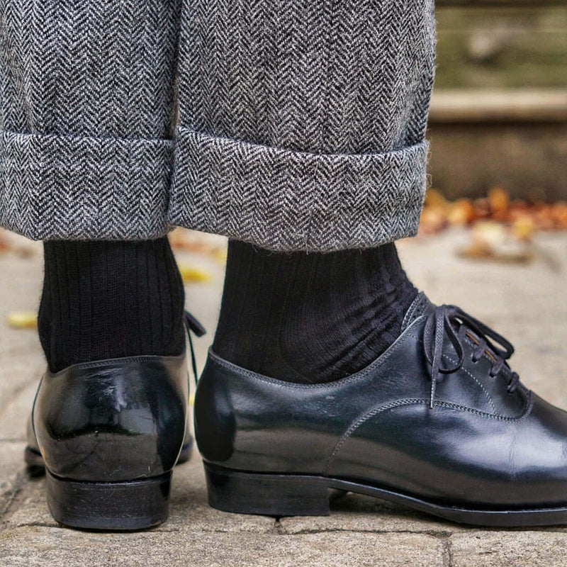 Man Wearing Black Merino Wool Dress Socks with Grey Herringbone Trousers and Black Dress Shoes