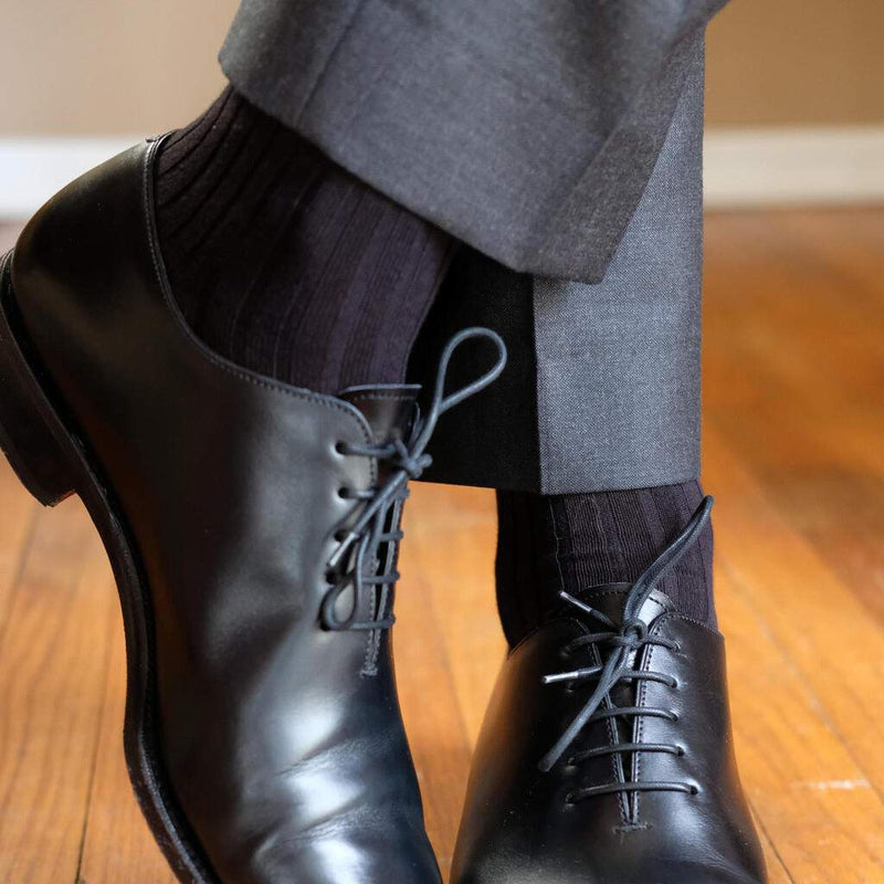Man Crossing Ankles Wearing Black Dress Socks with Charcoal Dress Pants and Black Dress Shoes