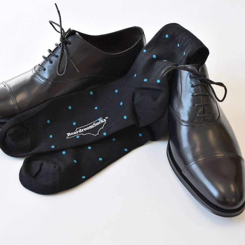 Pair of Black Over the Calf Dress Socks Decorated with Small Teal Blue Polka Dots Laying On Pair of Black Cap Toe Dress Shoes