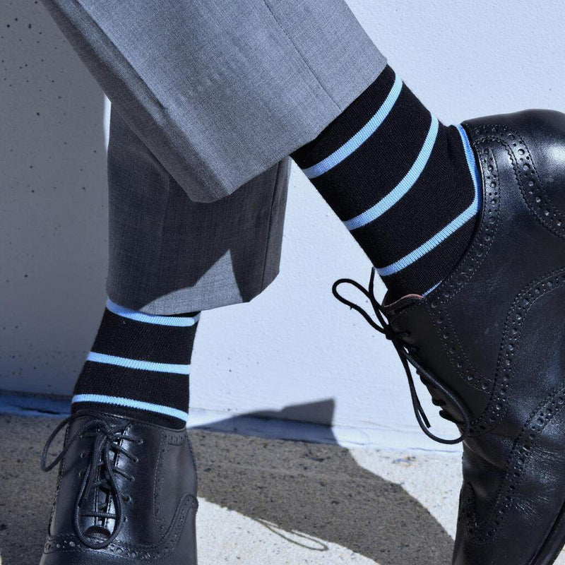 Man Crossing Ankles Wearing Black Dress Socks with Light Blue Stripes and Black Brogue Dress Shoes