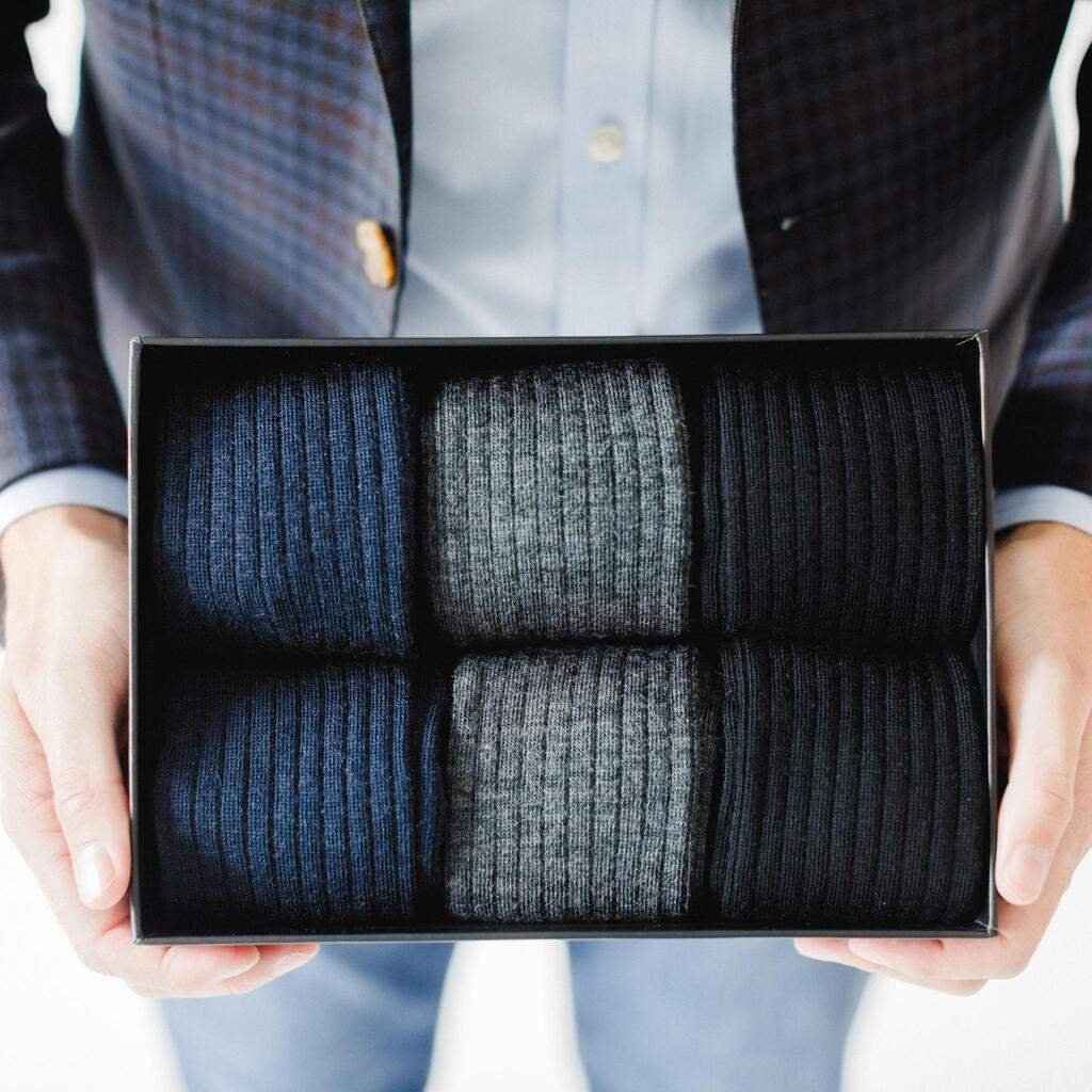 Man Wearing Sportcoat Holding Box Filled with Black Grey and Navy Dress Socks