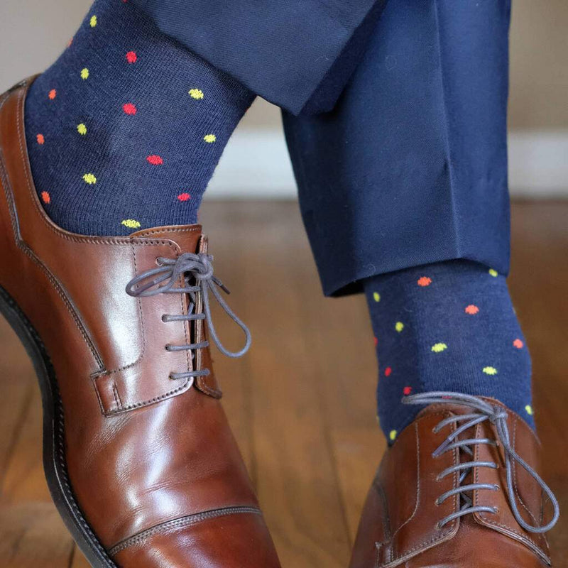 Man Standing with Legs Crossed Wearing Navy Blue Dress Socks Decorated with Colorful Polka Dots