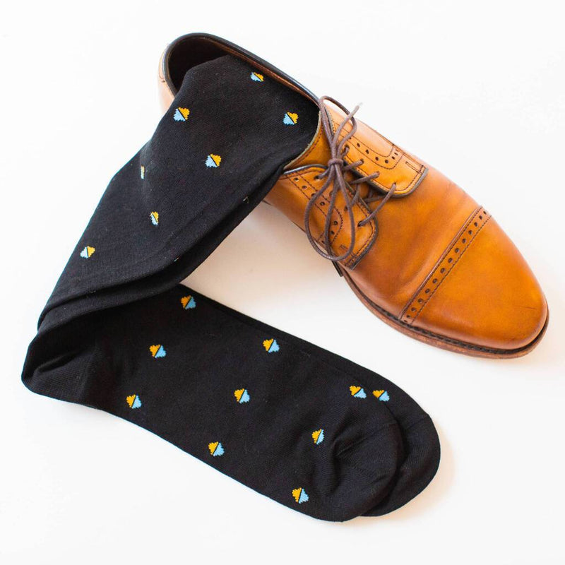 Pair of Black Over the Calf Dress Socks Decorated with Diamonds Laying On A Pair of Light Brown Dress Shoes