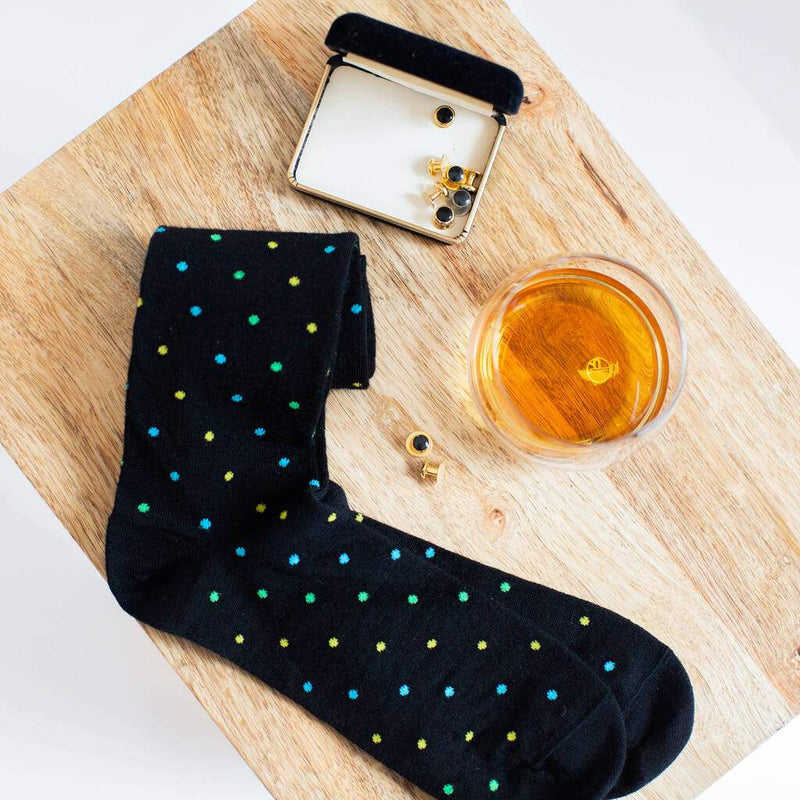 Pair of Black Patterned Dress Socks Sitting on a Stool with Cuff Links and a Glass of Bourbon