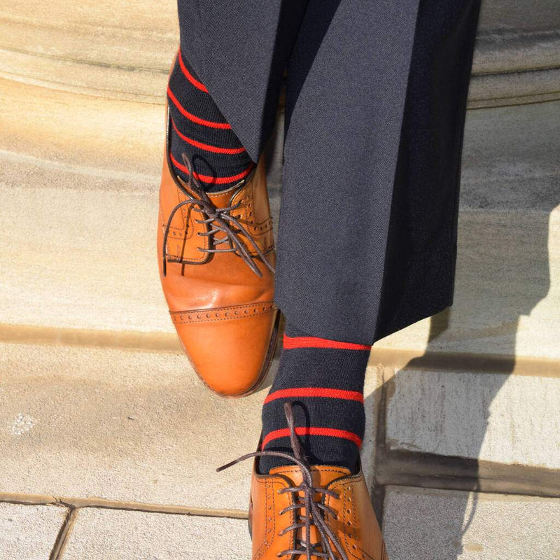 Man Wearing Navy Blue Dress Pants with Navy and Red Striped Dress Socks and Light Brown Dress Shoes