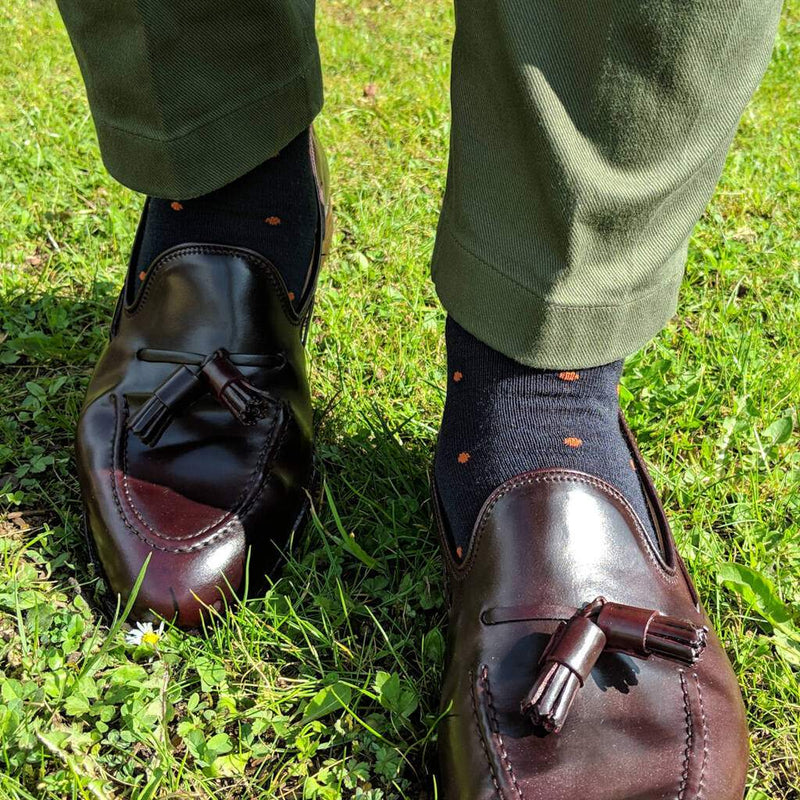Man Walking on Grass Wearing Olive Green Trousers and Navy Blue Dress Socks with Orange Dots and Dark Brown Tassel Loafers