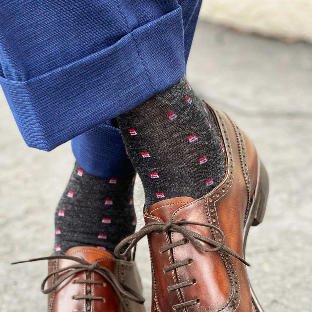 Man Wearing Charcoal Wool Patterned Dress Socks with Navy Blue Trousers and Brown Dress Shoes