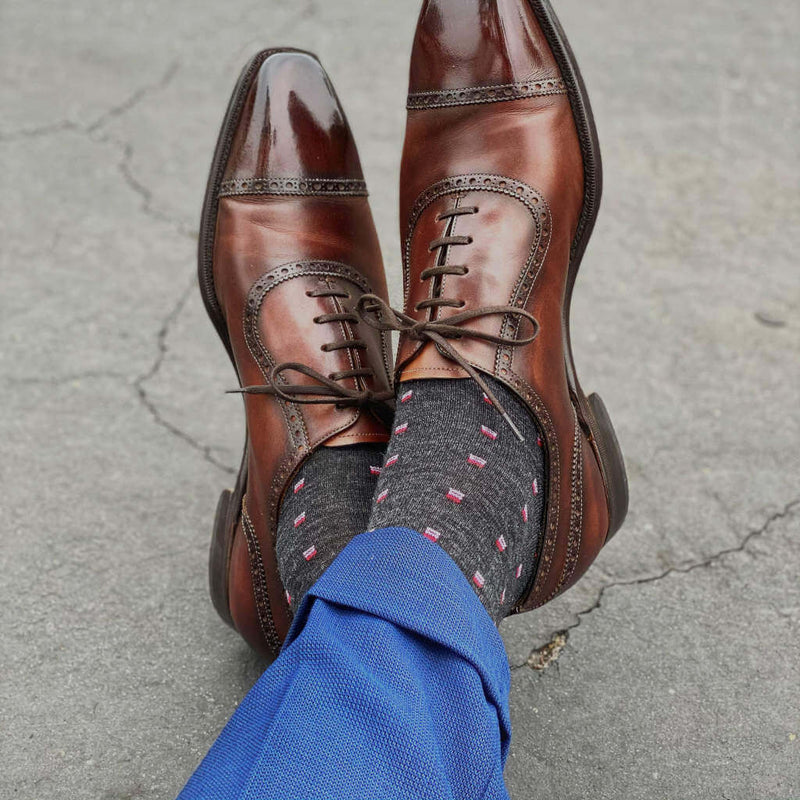 Man Crossing Ankles Wearing Charcoal Patterned Dress Socks with Navy Dress Pants and Brown Captoe Dress Shoes