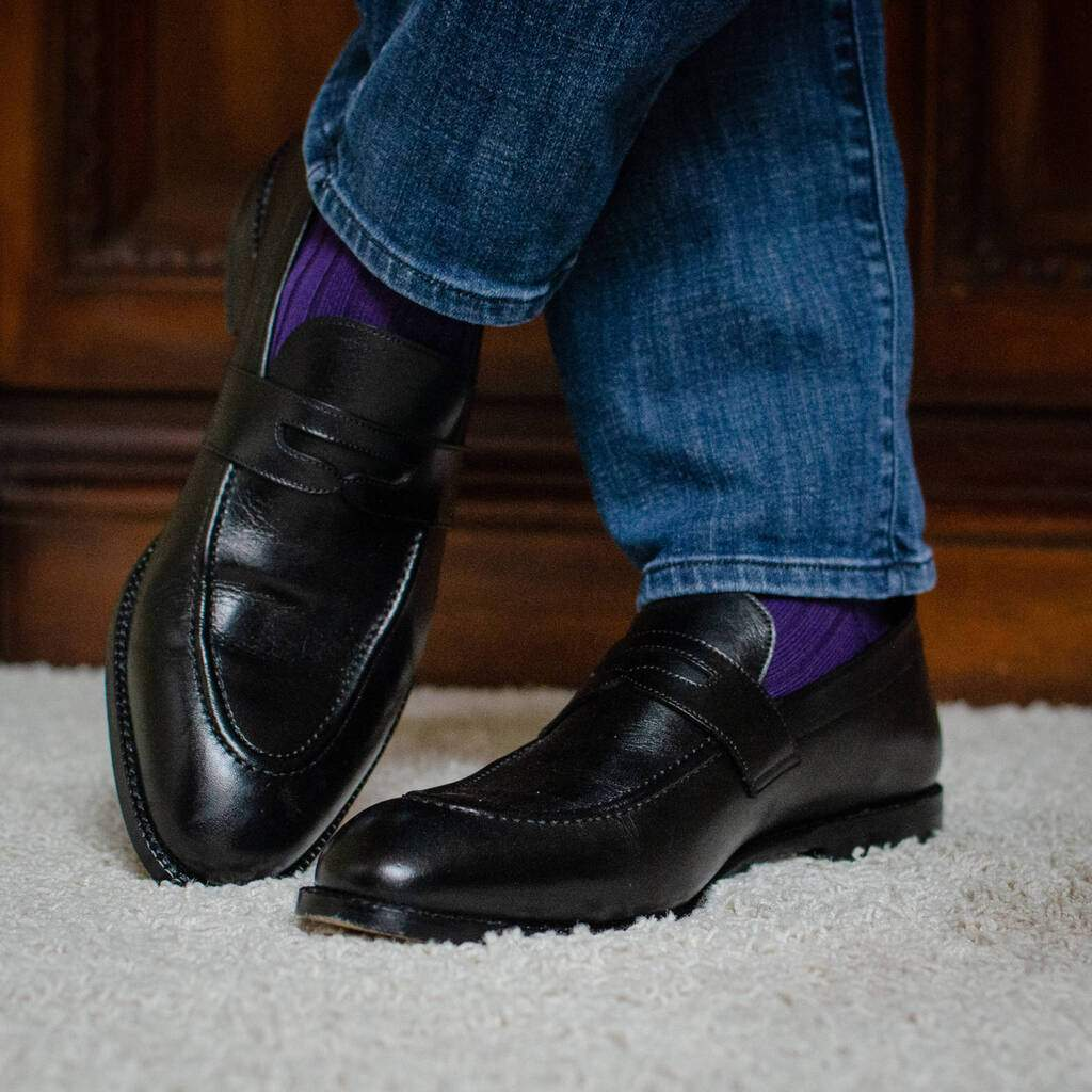 Man Standing On Plush Carpet Wearing Purple Dress Socks with Denim and Black Penny Loafers