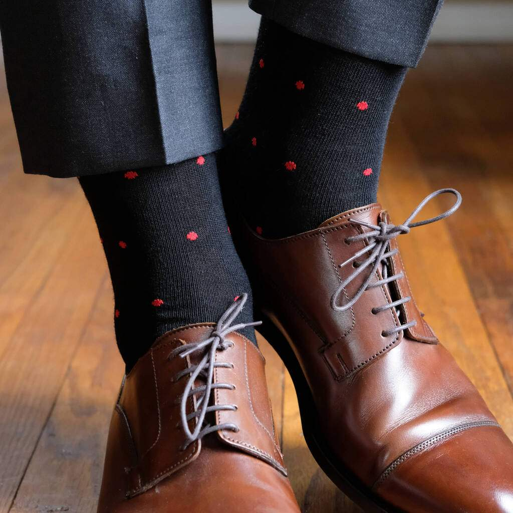 Man Wearing Black Wool Dress Socks with Red Dots and Dark Grey Dress Pants with Brown Dress Shoes