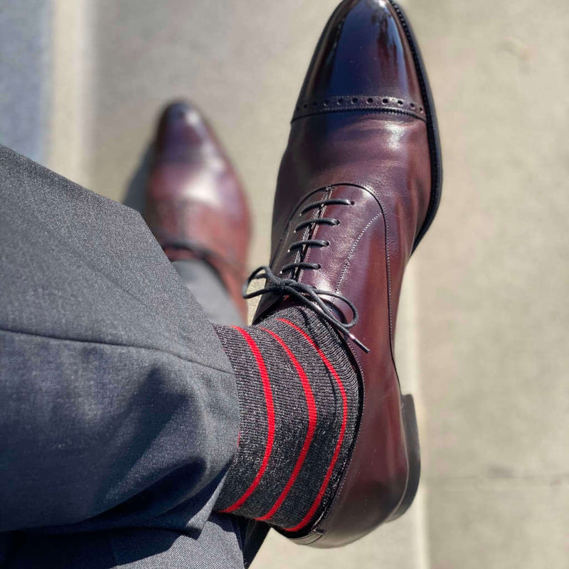 Man Crossing Legs Wearing Red Striped Dress Socks with Grey Dress Pants and Brown Dress Shoes