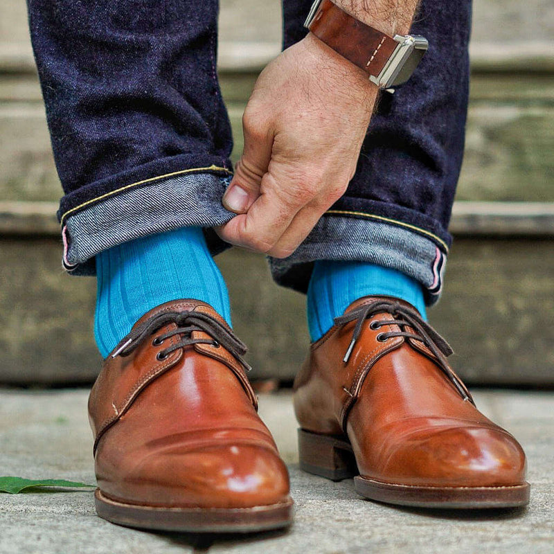 Man Adjusting Jeans Cuff While Wearing Teal Merino Wool Dress Socks and Light Brown Dress Shoes