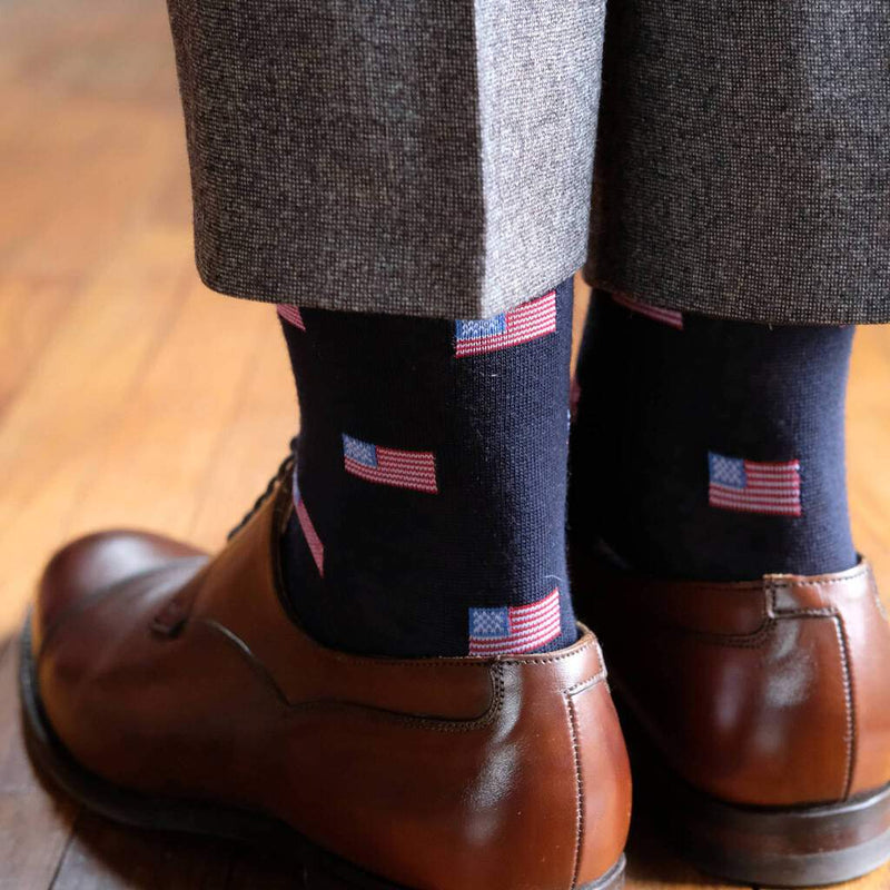Man Wearing Grey Dress Pants Light Brown Dress Shoes and Navy Blue Dress Socks Decorated with Small American Flags