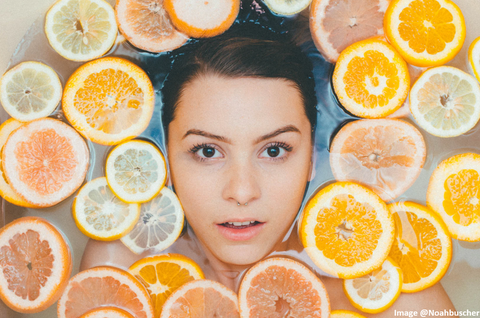 woman face up in bathtub with sliced oranges and a refreshed look on her face
